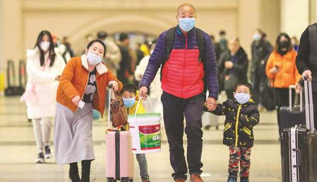 Commuters wearing face masks walk in Hankou railway station in Wuhan, in China's central Hubei provi