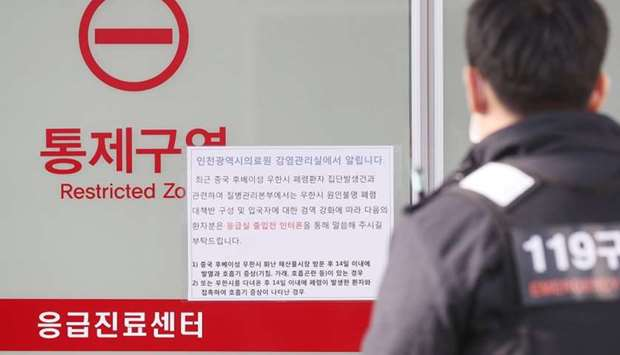 A rescue worker walks past a notice about new coronavirus that has broken out in China in Incheon, S