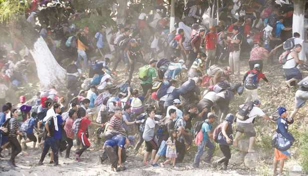 Central American migrants run after crossing the Suichate River, the natural border between Guatemal