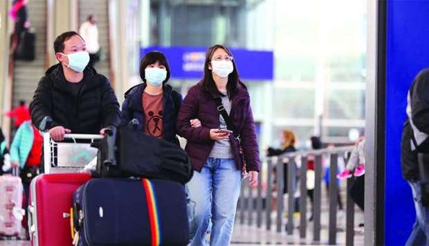 Travellers wearing face masks walk through the arrival hall at the Hong Kong International Airport