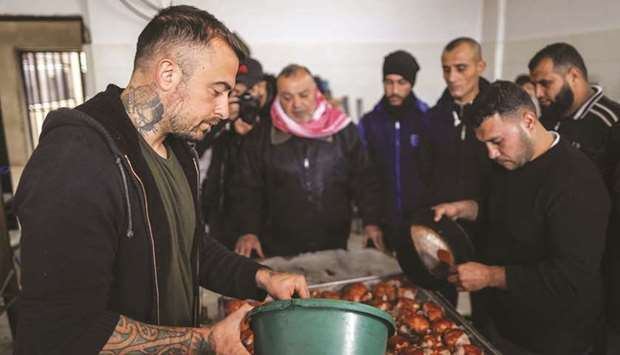 Gabriele Rubini (left), known as Chef Rubio, cooks with Palestinian prisoners at a Hamas-run civilia