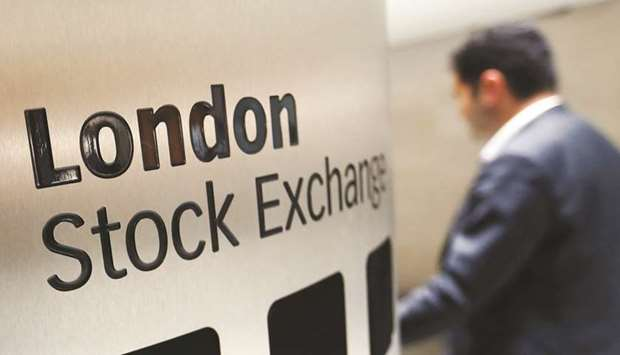 A visitor passes a sign inside the London Stock Exchange Group headquarters. The FTSE 100 ended the