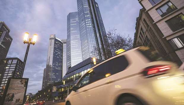 Automobiles pass the Deutsche Bank twin tower headquarters at dawn in Frankfurt. The bank has almost