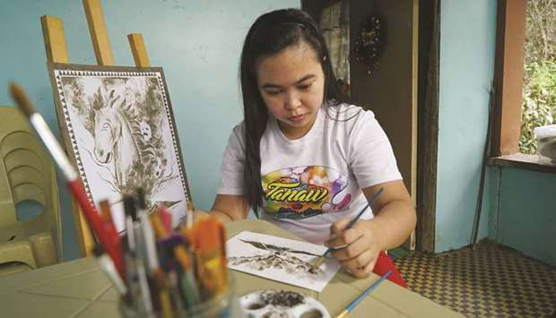 Filipina artist Janina Sanico uses volcanic ash she found in her yard to paint images of Taal volcan