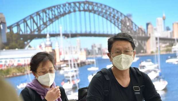 Passangers wearing masks arrive at Sydney airport
