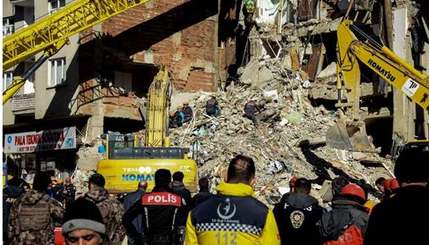 Rescue workers search for survivors in the rubble of a collapsed building after an earthquake hit El