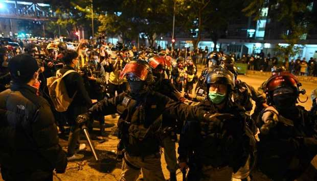 Riot police wearing facemasks gesture after residents set up barricades near the vacant Fai Ming Est