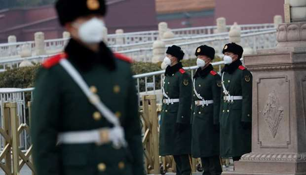 Paramilitary officers wearing face masks stand guard at the Tiananmen Gate, as the country is hit by