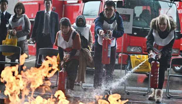 """Participants attend a """"fire extinguisher training"""" exercise during a """"disaster preparedness drill"""" o"""