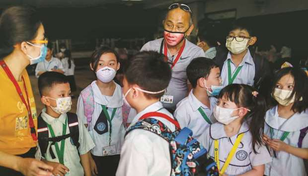 Guardians and students wear masks amid a health scare over a new virus that has infected thousands s