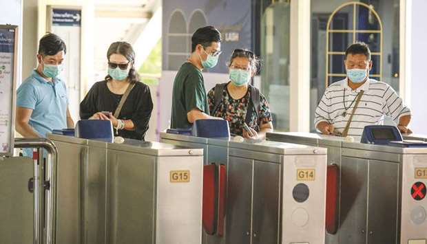 Chinese tourists wearing protective face masks leave the city commuter train station in Bangkok yest