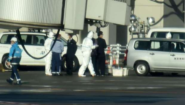 Workers in protective gear are seen on the apron near the first charter flight from the Chinese city
