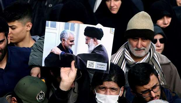 A demonstrator holds a picture of Supreme Leader Ayatollah Ali Khamenei with Iranian Major-General Q