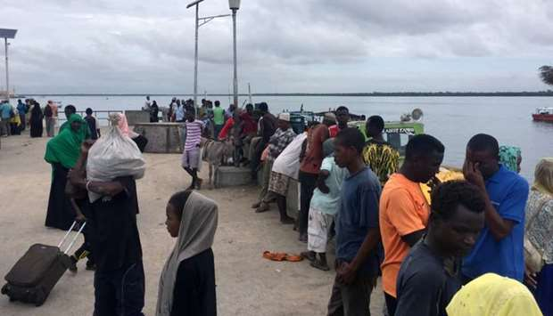Travellers are seen gathered at the Lamu jetty following an attack by Somalia's al Shabaab militants