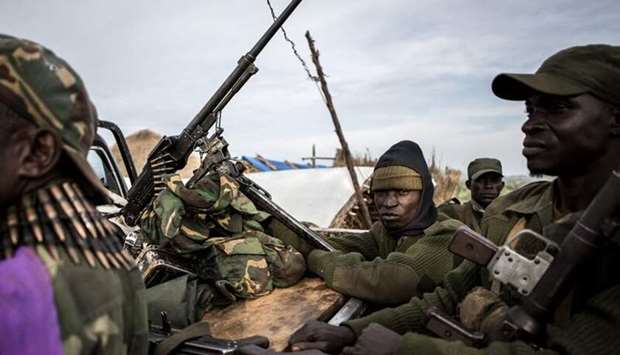 Soldiers of the Armed Forces of the Democratic Republic of the Congo (FARDC) sit in a truck bed in a
