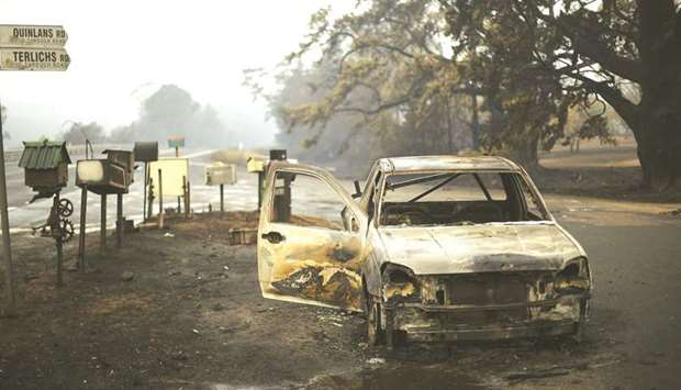 A burnt vehicle is seen on Quinlans street after an overnight bushfire in Quaama in Australia's New