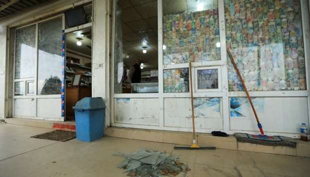 A man looks at a shattered glass window of a shop, caused by a missile launched by Iran on the US-le