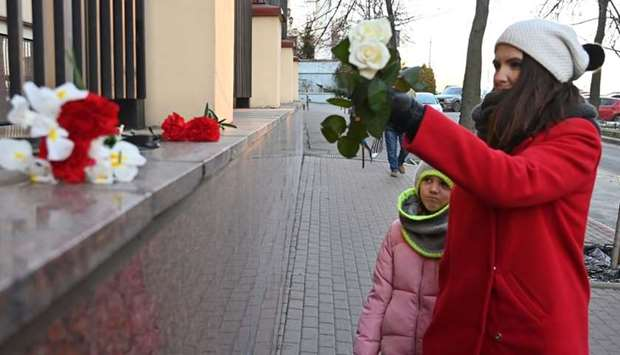 A woman with her daughter lay flowers outside the Canadian Embassy in Kiev on January 8, 2020 in rem