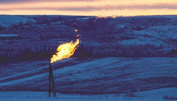 A natural gas flare on an oil well pad burns as the sun sets outside Watford City, North Dakota (fil