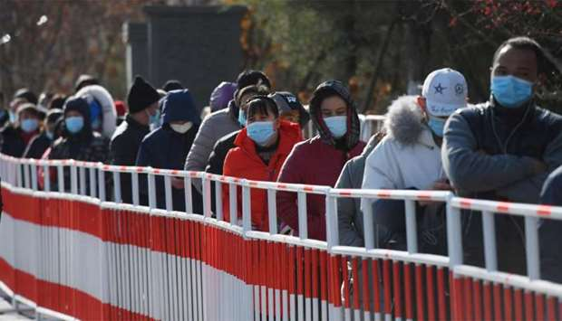 Residents line up to be tested for the Covid-19 coronavirus in Beijing