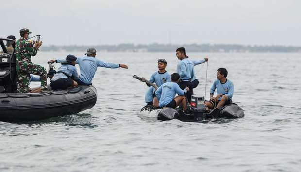 Indonesian Navy personnel are seen on boats during recovery operations for the Sriwijaya Air Flight