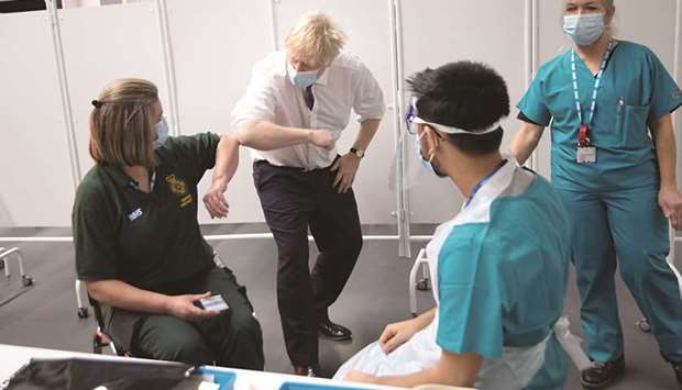 First Responder Caroline Cook elbow-bumps Prime Minister Johnson while she waits for her vaccination