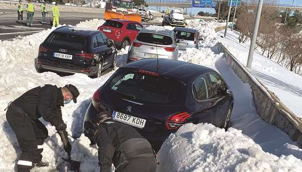 Members of Spain's military unit (UME) shovel snow to open a pass next to cars accumulated on M-40 h