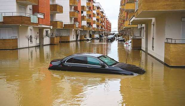 A car is seen submerged on a flooded street in the Kosovo town of Fushe Kosove after heavy rain and