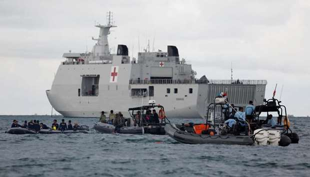 Indonesian navy divers and other rescue members stand on rubber boats next to KRI Semarang, during t