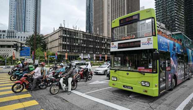 Motorists make their way on a street in Kuala Lumpur, as Malaysian authorities were set to impose ti