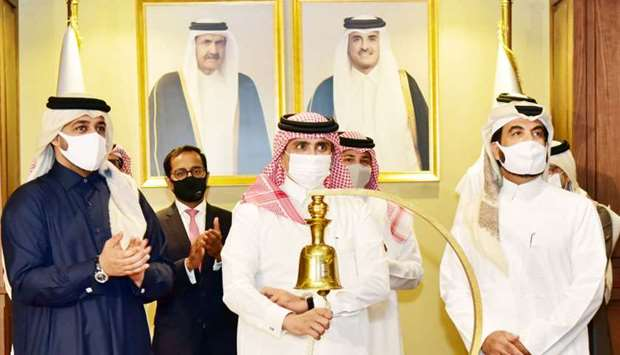 Al-Suwaidi rings the bell to mark the advent of it in the QSE in the presence of al-Mannai, al-Manso