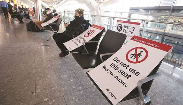 Social distancing signs are displayed on seats in the check-in area at the Heathrow Airport in Londo