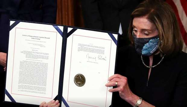 US House Speaker Nancy Pelosi (D-CA) shows article of impeachment against President Donald Trump.