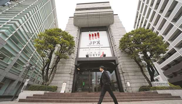 A pedestrian walks past the Tokyo Stock Exchange building. The Nikkei 225 closed 0.6% down at 28,519