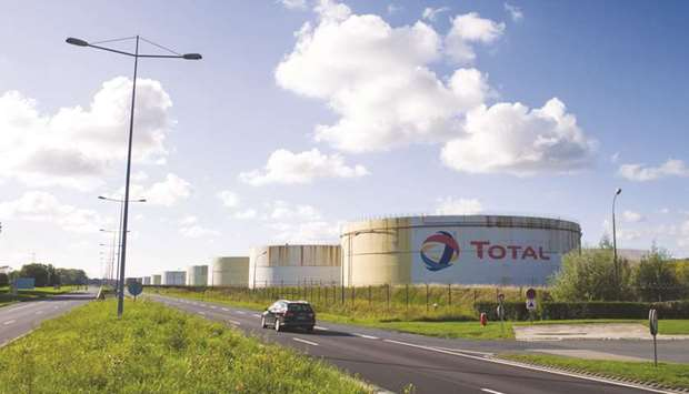 An automobile passes storage silos at the Total SE petrochemical plant in Le Havre, France. Total sa
