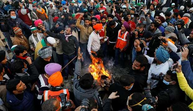 Farmers burn farm law copies in a bonfire as they celebrate the Lohri festival, at the site of a pro