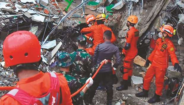 Rescuers search for survivors at a collapsed building in Mamuju in Sulawesi Island.