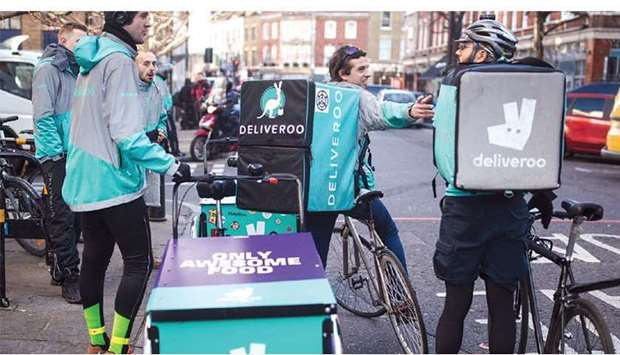 Food delivery cycle couriers chat as they wait for orders from Deliveroo in London. As lockdowns res