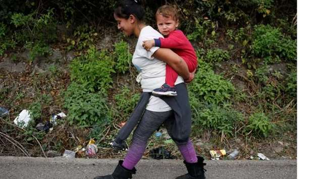 A Honduran woman carries a child as she takes part in a new caravan of migrants, set to head to the