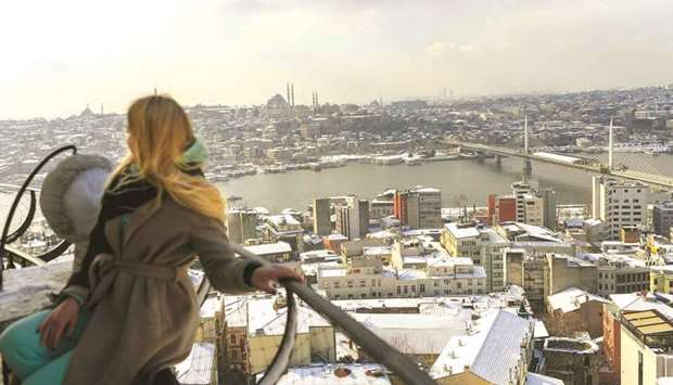 A woman stands on top of the Galata Tower as roofs are covered with snow yesterday in Istanbul. Turk