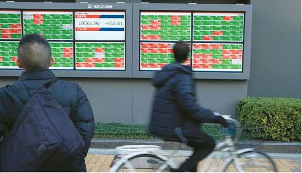 A pedestrian and a man riding his bicycle look at an electronic stock board outside a securities fir