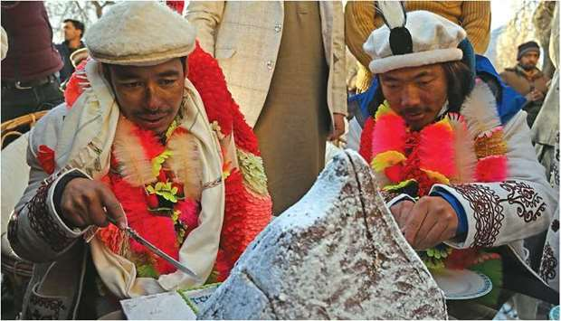 MILESTONE: Nepal's climbers Nirmal Purja, left, and Mingma Sherpa cut a cake upon their arrival afte