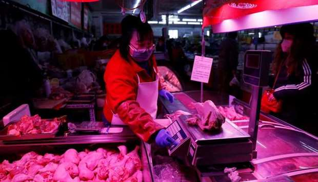 A vendor wearing a face mask following the coronavirus disease outbreak weighs a chicken at her stal