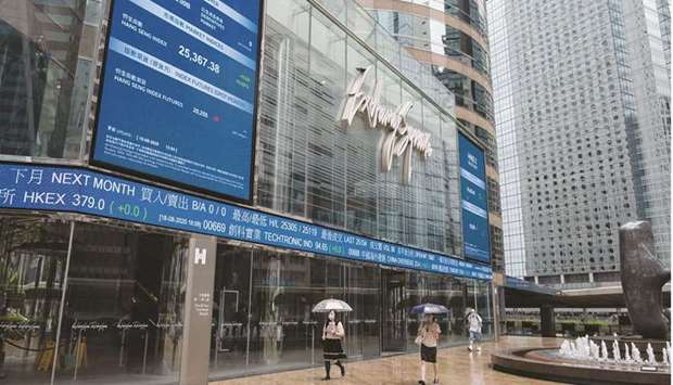 Pedestrians walk past the Exchange Square complex, which houses the Hong Kong Stock Exchange. The Ha