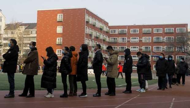 People line up to get their nucleic acid test on the sports ground of a school following the outbrea