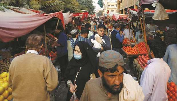 This picture taken last week shows people with and without masks walk along fruit stalls at a market