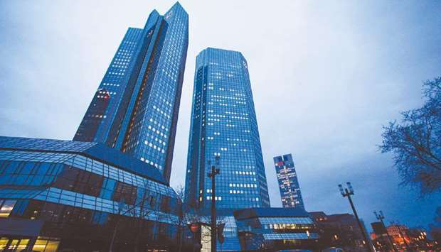 Lights illuminate the windows of Deutsche Bank headquarters in Frankfurt. Deutsche Bank and Barclays