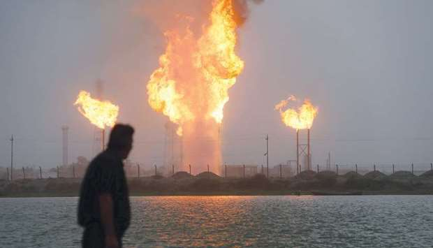 A man looks at flames rising from oil refinery pipes in Basra (file). Opec's second-biggest producer