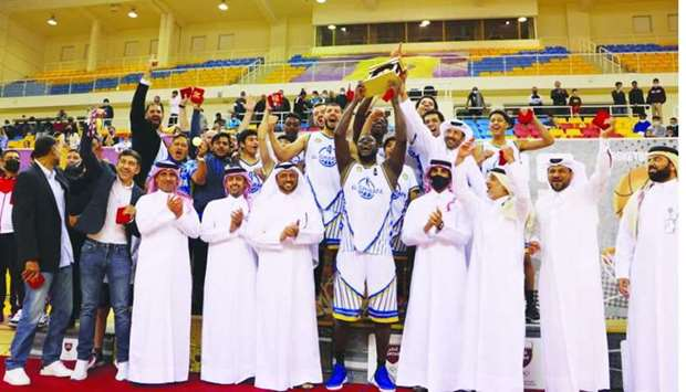 Al Gharafa players and officials celebrate with the winners' trophy and Qatar Basketball Federation