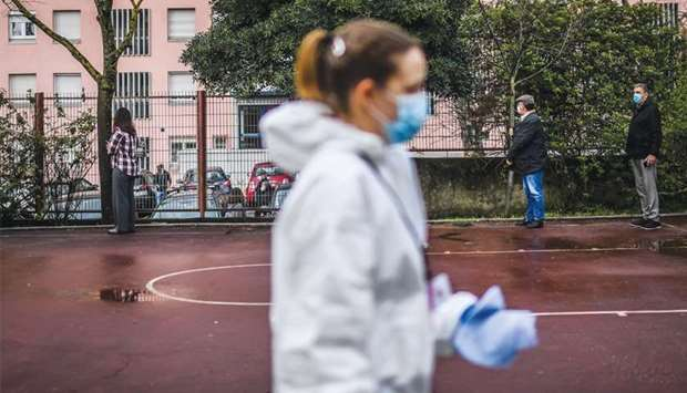 A cleaning employee walks past people queuing to vote in the Portuguese presidential election, at Li